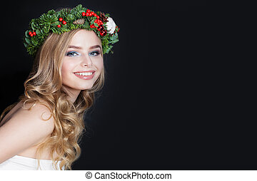 Smiling woman with blonde hair and green fir wreath on black background