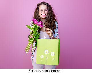 smiling woman with bouquet of flowers showing shopping bag