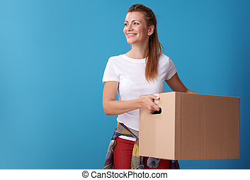 smiling woman with cardboard box looking at copy space on blue