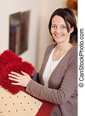 Smiling woman with carpet samples displayed in her hands in...