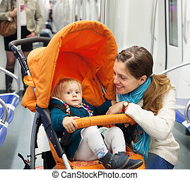 woman with child in stroller at subway