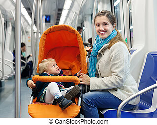 Smiling woman with child in subway train