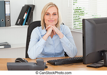 Smiling woman with chin on her hands behind a desk