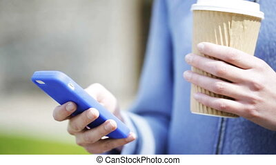 smiling woman with coffee cup and smartphone