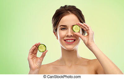 smiling woman with cucumber over green background