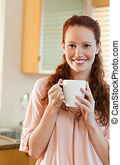 Smiling woman with cup in her hands