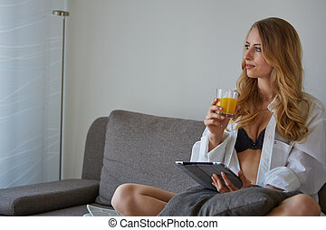 smiling woman with cup of coffee reading magazine