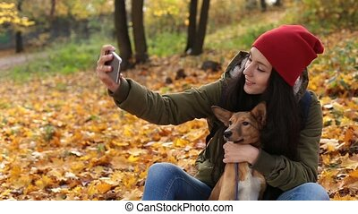 Smiling woman with dog taking selfie in autumn
