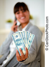 Smiling woman with dollars talking on mobile phone
