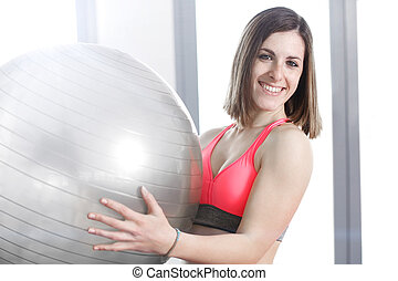 smiling woman with exercise ball in gym.