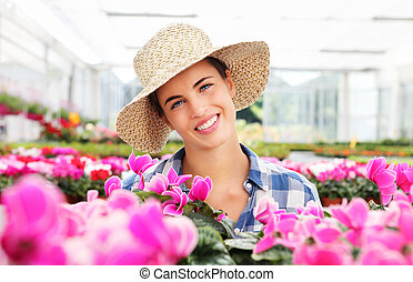 smiling woman with flowers, in greenhouse, cyclamen plants