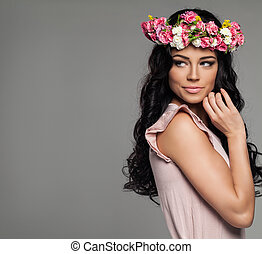 Smiling Woman with Flowers on Background with Copy space. Brunette Beauty