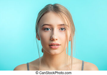 Smiling woman with fresh clean skin posing over blue background