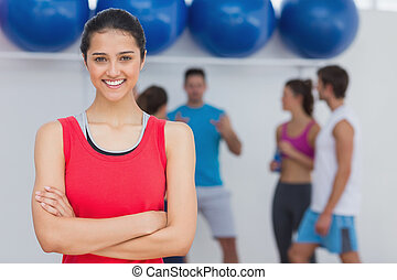 Smiling woman with friends in background at fitness studio -...