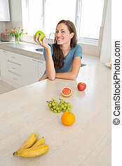 Smiling woman with fruits on counter in kitchen