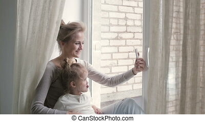Smiling woman with girl taking selfie