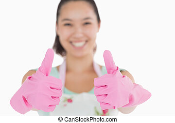 Smiling woman with gloves giving thumbs up
