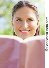 Smiling woman with her book in the park