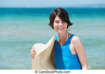 Smiling woman with her sunhat at the seaside