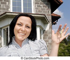 smiling woman with keys to the new house