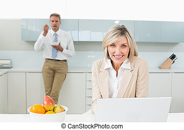Smiling woman with laptop and man in background at kitchen