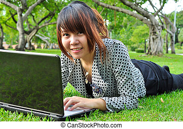 Smiling woman with laptop in nature