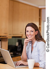 Smiling woman with laptop in the kitchen