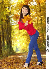 Smiling woman with maple leaves in hand