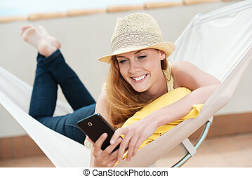 Smiling Woman With Mobile Phone In Hammock