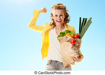 smiling woman with paper bag with groceries showing biceps against blue sky