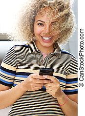 Smiling woman with phone and wind in hair