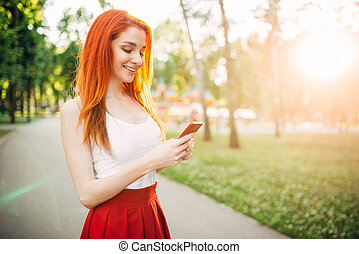 Smiling woman with phone outdoor in park on sunset
