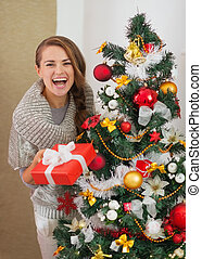 Smiling woman with present box looking out from Christmas tree