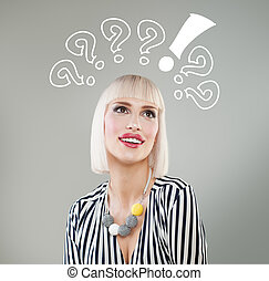 Smiling woman with questions mark above head looking up