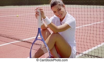 Smiling Woman with Racket Sitting on Tennis Court - Full...