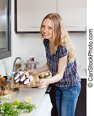 Smiling woman with raw seabass fish