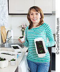 Smiling woman with seedlings