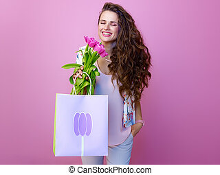 smiling woman with shopping bag enjoying bouquet of tulips