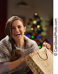 Smiling woman with shopping bag in front of Christmas tree