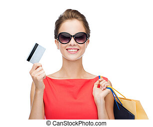 smiling woman with shopping bags and plastic card -...