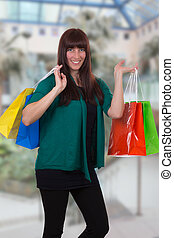 Smiling woman with shopping bags in a mall