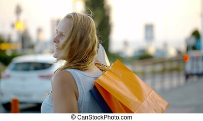 Smiling woman with shopping bags outdoor
