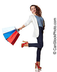 Smiling woman with shopping bags posing on white background