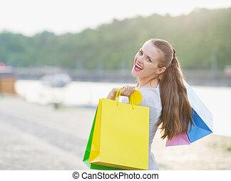 Smiling woman with shopping bags walking embankment