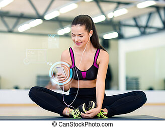 smiling woman with smartphone and earphones in gym - fitness...