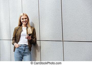 Smiling woman with smartphone looking camera
