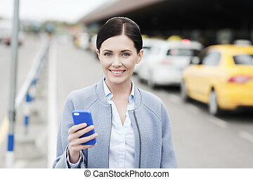 smiling woman with smartphone over taxi in city - travel,...