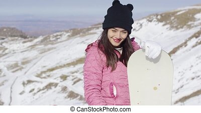 Smiling woman with snowboard in mountains - Half body...