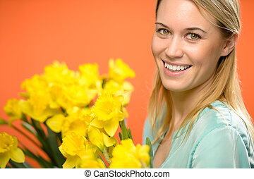 Smiling woman with spring yellow narcissus flowers