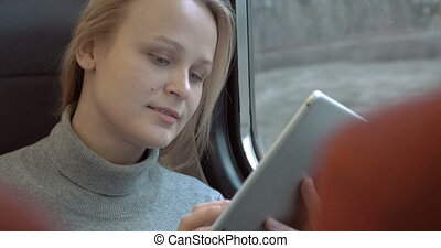 Smiling Woman with Tablet in Train